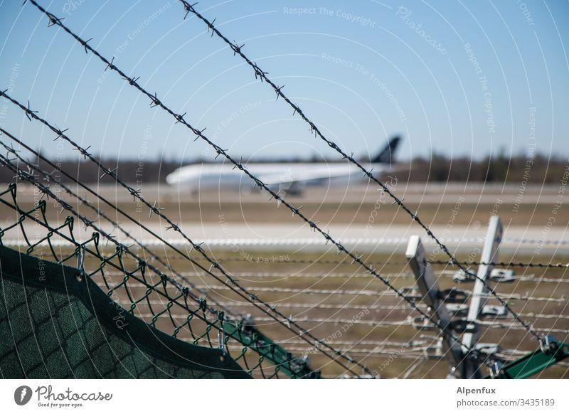 angestachelter Zaun hinter dem ein verschwommenes Flugzeug parkt Stacheldrahtzaun Außenaufnahme Flughafen Sicherheit Grenze Barriere Menschenleer Farbfoto