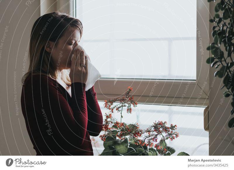 Junge kranke Frau schnäuzt sich am Fenster in ein Taschentuch 30s Erwachsener Allergie allein Appartement blasend Pflege lässig Kaukasier kalt Ansteckung dunkel