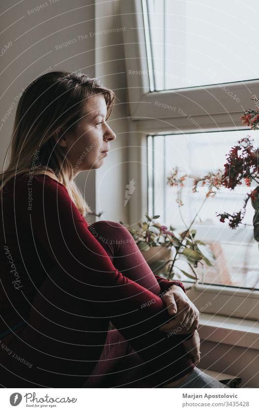 Junge besorgte Frau schaut durch das Fenster Erwachsener allein Anspannung Appartement Kaukasier COVID19 deprimiert Depression unzufrieden Distanzierung
