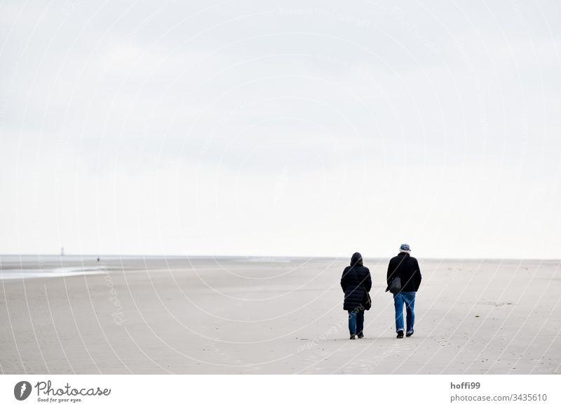 Strandspaziergang im Winter pärchen Sand Sandstrand Paar Nordseeküste Wattenmeer Ferien & Urlaub & Reisen Insel seichtes Wasser Küste Horizont Brandung
