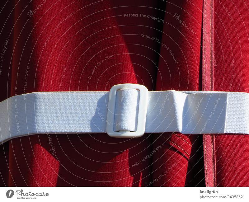 Detailaufnahme von weißem Gurt der roten Sonnenschirm zusammen schnürt Gürtel Zusammenhalt Gürtelschnalle Schnalle Stoff Licht Schatten Farbfoto Naht