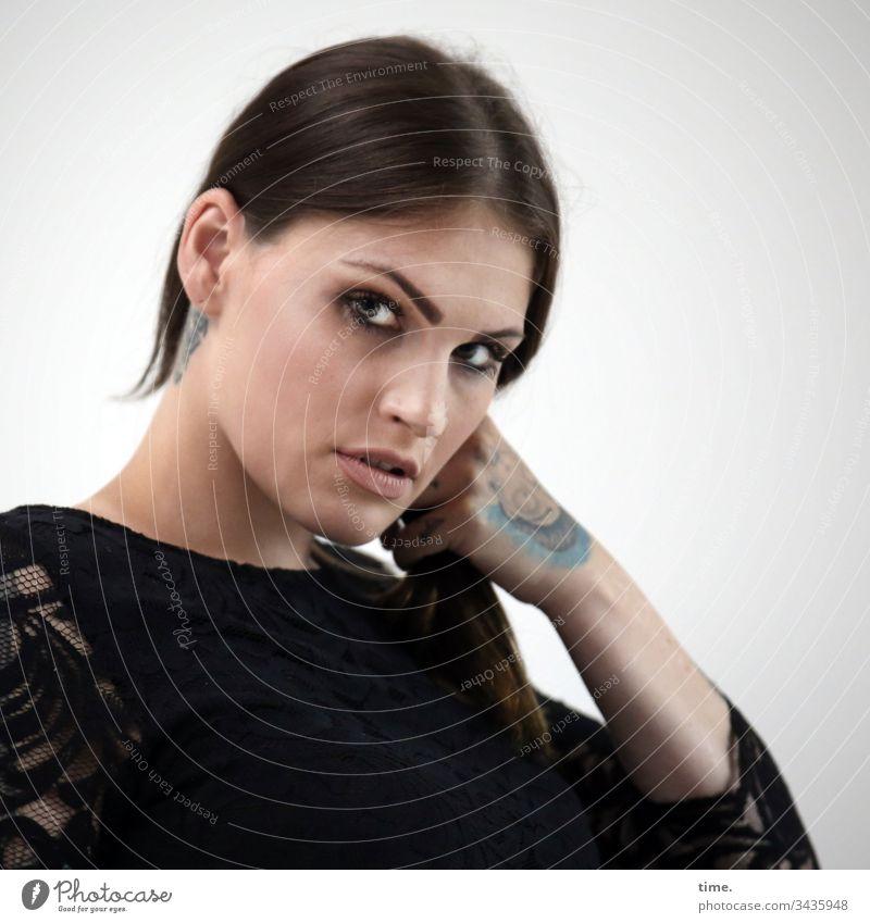 mixed emotions Frau feminin weiblich skeptisch langhaarig zopf tattoo kleid intensiv portrait blick halbprofil halten freisteller wand misstrauisch