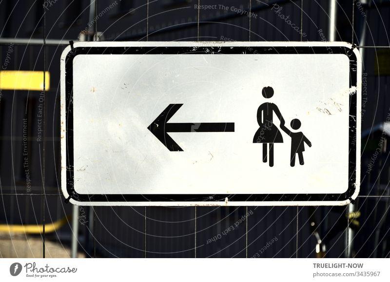 An einem Absperr-Gitter ein weisses Hinweis-Schild für Fußgänger mit schwarzem Piktogramm, das einer stilisierten Frau mit kleinem Kind an der Hand durch einen Pfeil signalisiert: Weitergehen nach Links. | Corona Thoughts