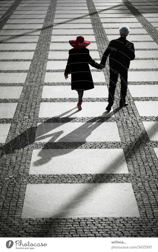 Und am Abend gehen wir ins Theater Paar Mann Frau Dame Hut Menschen Händchenhalten öffentlicher Platz Schatten flanieren spazieren Zusammensein Partnerschaft