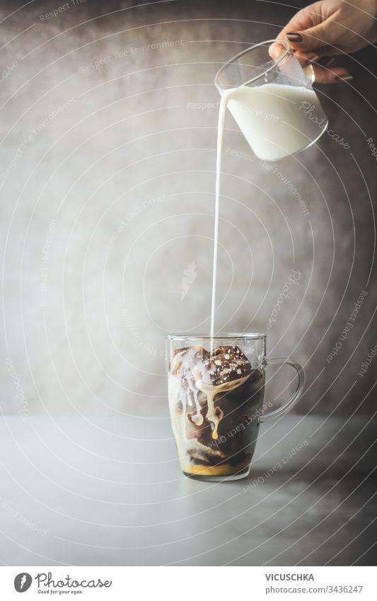 Zubereitung von Eiskaffee. Weibliche Hand gießt Sahne-Milch in Glas mit Kaffee-Eiswürfeln auf rustikalem Tisch im Betonwandhintergrund. Zubereitung von Eiskaffee. Erfrischendes Sommergetränk. Kaltes Getränk.
