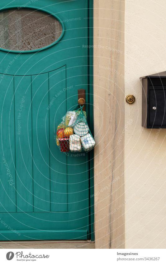 kontaktlose Lieferung Einkauf während der Quarantäne. Einkaufstasche, Einkaufsnetz Einkäufe und Lebensmitteln hängt an der Haustür, Nachbarschaftsunterstützung - Konzept zur Quarantänezeit wegen Coronavirus-Infektion Covid-19