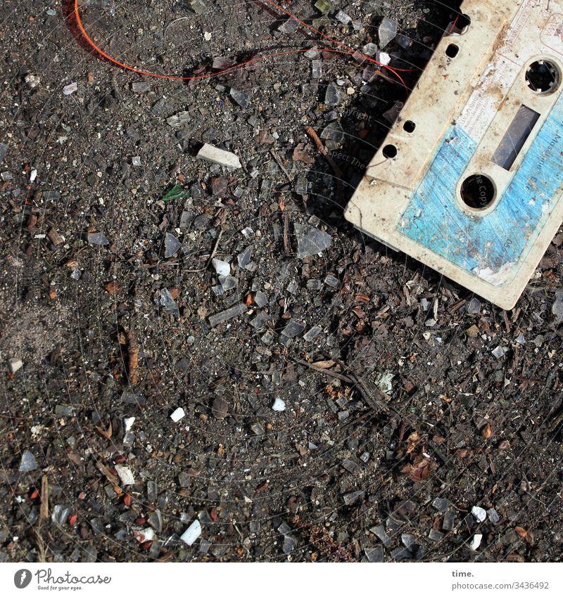 süße kleine verdreckte Audiokassette kunststoff schatten sonnenlicht abdruck dreckig schmutzig detail linien oberfläche trashig kaputt sandig teerboden cassette