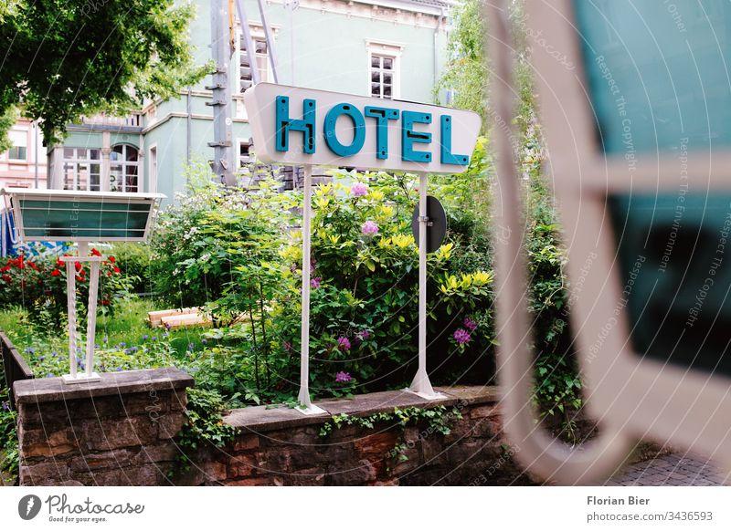 Typografisches Hotelschild an einem blühenden Garten in einer Einfahrt Typographie Buchstaben Schilder & Markierungen Zeichen Werbung Wort Hinweisschild