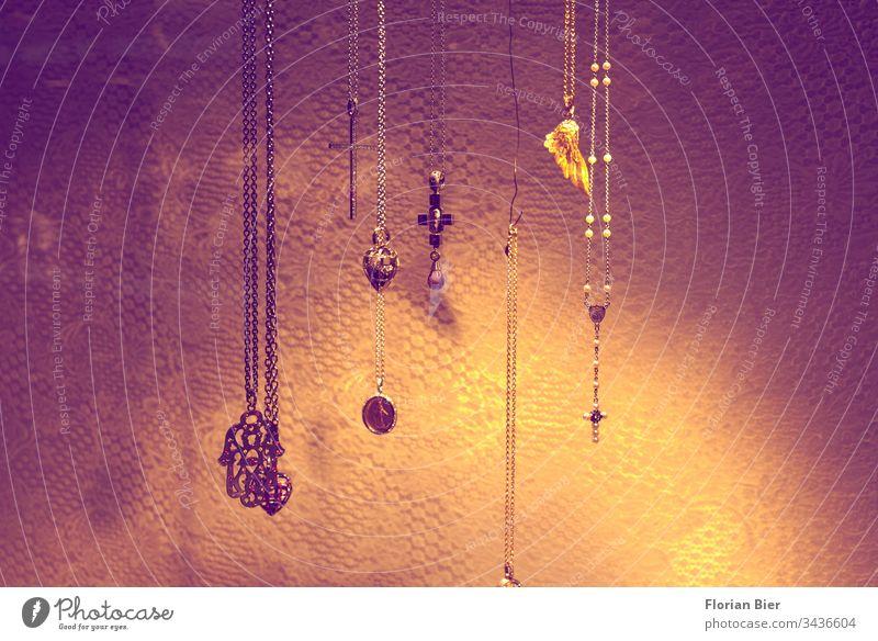 Beleuchtet und ausgestellter Schmuck mit religiösen Symbolen in Form von Ketten und Anhängern Schmuckanhänger Halskette Religion & Glaube Symbole & Metaphern