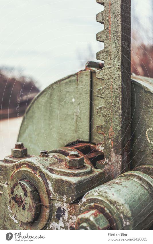 Teil einer schweren Maschine aus Stahl mit Rost und Patina Industrie Zahnrad massiv Maschinenteil verrostet Textur Legierung grün Schraube Schraubenmutter