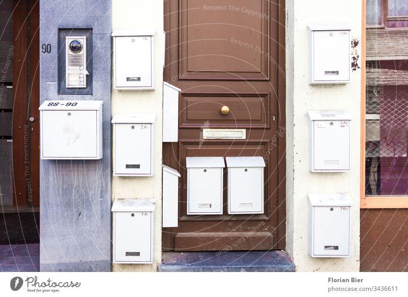 Aussen angebrachte Briefkästen an einem Wohnhaus mit Eingangstüre Briefkasten Briefkastenschlitz Post Tür Haus schreiben Stadt Metall Wand Fassade Gebäude
