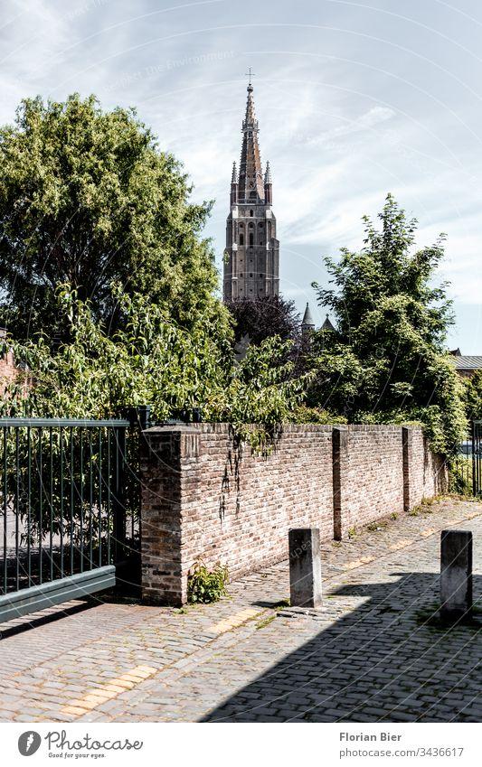 Schmale gepflasterte Straße vor einer Hofeinfahrt in Brügge mit Blick auf die Liebfrauenkirche Baustil Stadtzentrum Europa Architektur Gebäude Tourismus alt