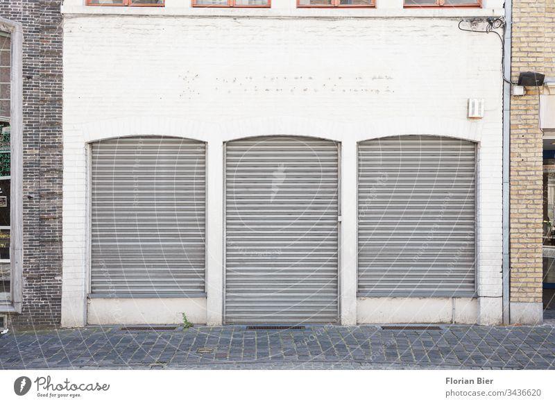 Geschlossenes Ladengeschäft mit herunter gelassenen Rolläden in einer altertümlichen Fassade Geschäft geschlossen Rolladen Krise Fenster Tür Einzelhandel