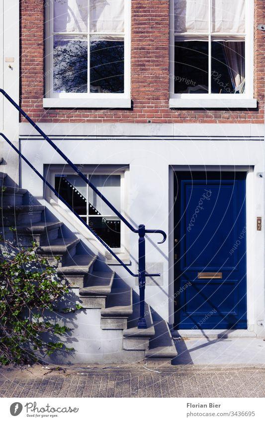 Eingang eines Wohnhauses mit einer kräftig blauen Eingangstür im Amsterdamer Krachtenviertel Niederlande Haus Fenster Fassade Victorianisch Baustil Gebäudeteil