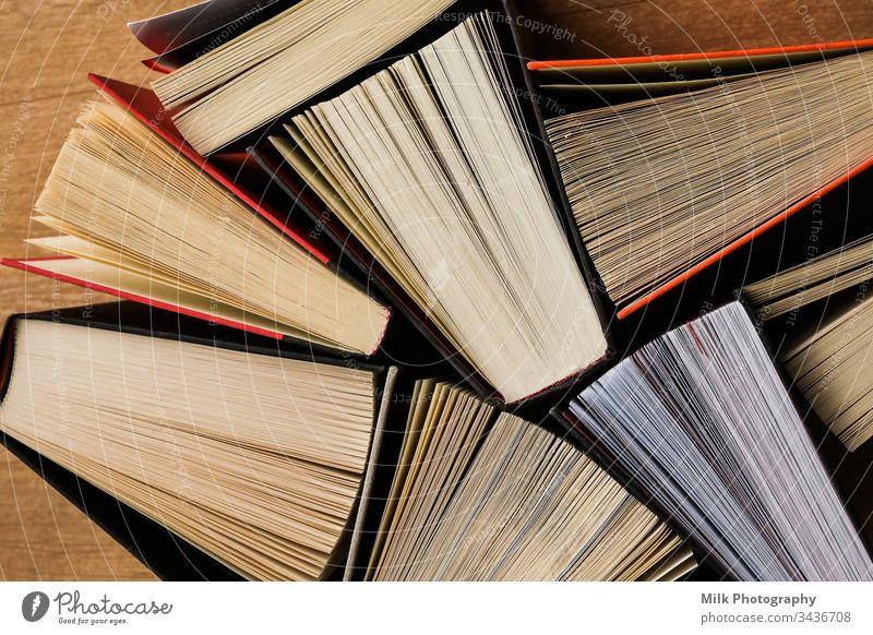 Bunte, dicke, aufgeschlagene Bücher stehen auf einem hölzernen Hintergrund vertikal niemand Farbe Foto Bild gestylt Brühe copyspace Platz für Text Textfreiraum