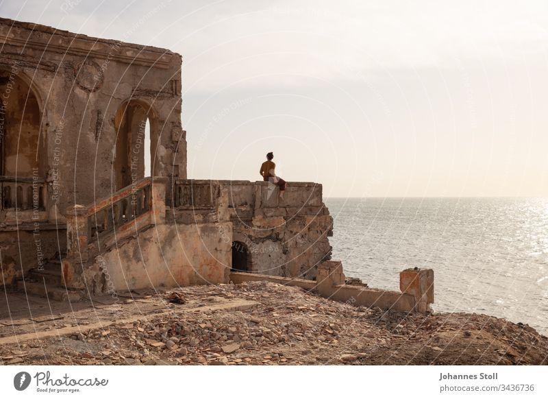 Junge Frau sitzt auf Mauerbrüstung einer Ruine und blickt aufs Meer Ozean Wasser Strand Küste Trümmer Steine Fels Mauerwerk Architektur Tempel Burg Schloss
