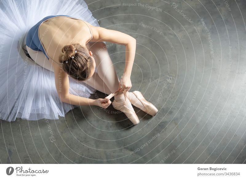 Draufsicht auf eine Balletttänzerin, die sich Hausschuhe um den Knöchel bindet Fußknöchel Künste Ballerina Kaukasier Klassik Tracht Tanzen Eleganz Frau Mädchen