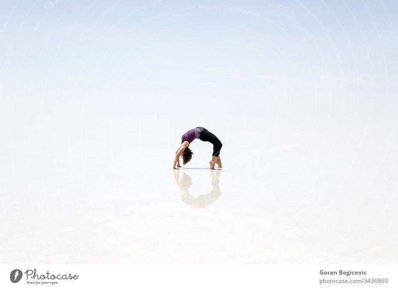 Junge Frau in der Salar de uyuni-Salzfläche in Bolivien Kunstturnen altiplano Höhe amerika Anden Gegend blau hell Windstille Farbe Tag wüst Ausflugsziel