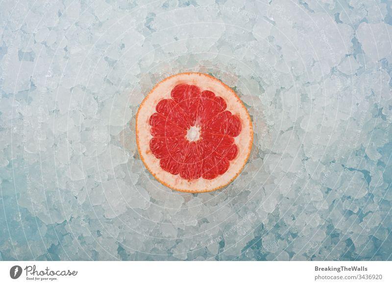 Frische rosa Grapefruitscheibe über zerstoßenem Eis rot eine Hälfte geschnitten Scheibe frisch zerdrückt Hintergrund Nahaufnahme blau weiß kalt gefroren Frucht