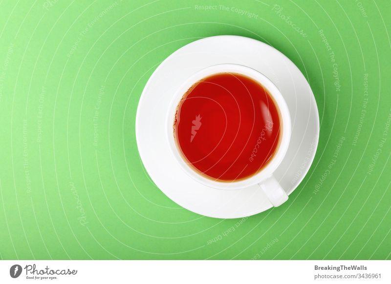 Weiße Tasse schwarzer oder roter Früchtetee über grünem HINTERGRUND Tee Frucht Aufguss weiß Untertasse Papier Pastell Hintergrund Nahaufnahme erhöht Top Ansicht