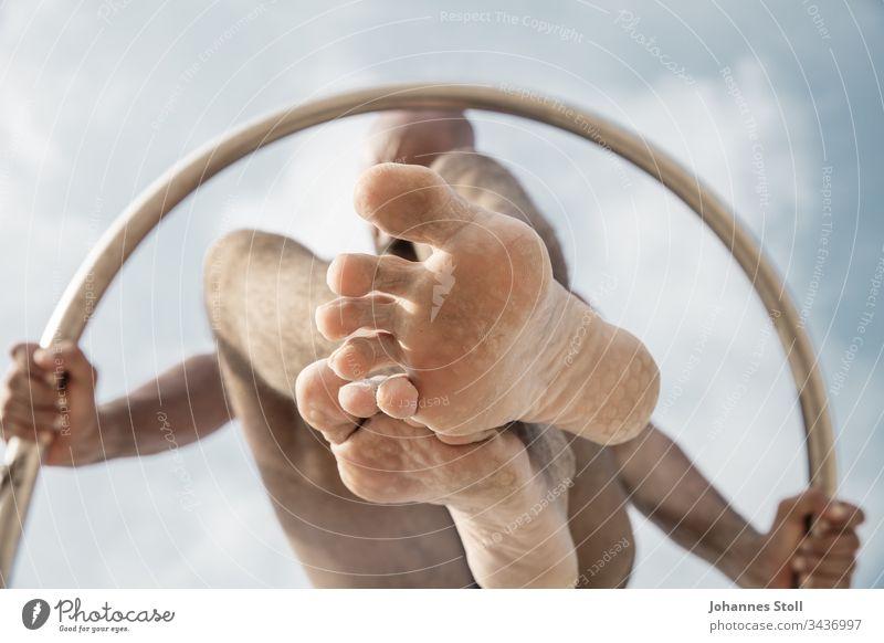 Turnender Mann mit Ring von unten vor blauem Himmel Körper Arme Hände Füße Zehen Knie Akrobatik halten Wolken Kreis Chrom Edelstahl Klettergerüst Spiel Tanz