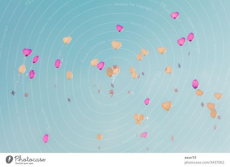 Herz-Liebes-Ballons fliegen mit Zeremonie-Wünschen in den türkisfarbenen Himmel. Romantisches Symbol für eine zukünftige Partnerschaft. Gruppe von schönen Herzballons mit Glückwunschkarten bei der Hochzeitsfeier oder am Valentinstag