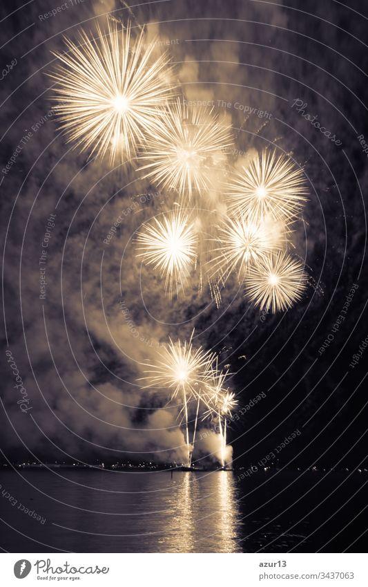 Luxus-Feuerwerk-Veranstaltung Himmel-Wasser-See-Show mit gelben Sternen. Hochwertiges Unterhaltungs-Zauber-Sternfeuerwerk z.B. zu Silvester oder zur Feier des Unabhängigkeitstages. Schöne Spiegelungen auf der Seeoberfläche