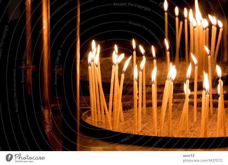 Gruppe von gelben Kerzen in der Kirche für das Auferstehungsgebet des Glaubens. Kerzenschein-Feuerflammen in Kreisreihen sind religiöses Symbol für Frieden, Leben und Seelenstille. Nachruf Hoffnungsopfer gegen die Trauer