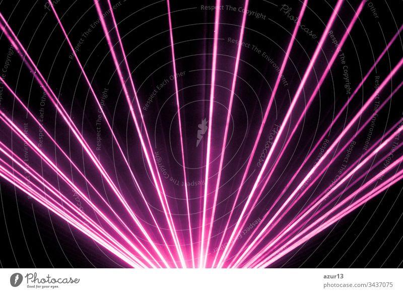 Die Bühne des Nachtclubs mit rosa Lasershow und glänzenden, funkelnden Strahlen. Luxuriöse Unterhaltung in Nachtclub-Veranstaltungen, Festivals, Konzerten oder an Silvester. Strahlenstrahlen sind Symbol für Wissenschaft und Universumsforschung