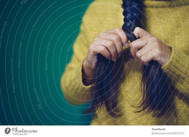 Mädchen flechtet ihr Haar Behaarung Geflecht Frau geflochten schön brünett Frisur grün gelb Porträt Schönheit Zopf jung weiß Mode Gesicht attraktiv Hintergrund