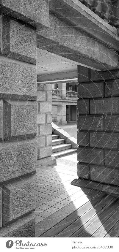 Durchgang in altem Gemäuer zu einer Treppe und anderen Gebäudeteilen Mauer Mauerstein Balkon imposant herrschaftlich schwarz-weiss mustermix Menschenleer Tag