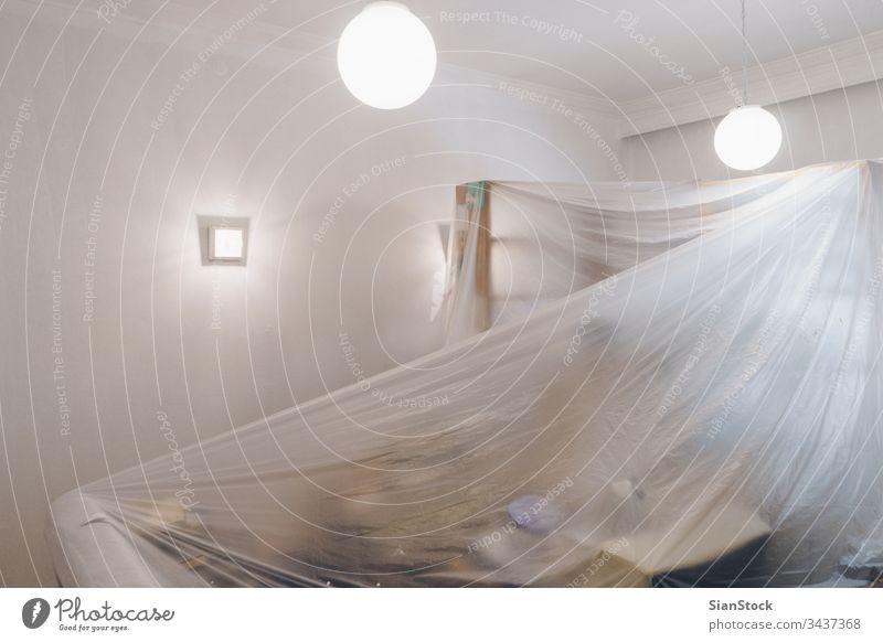 Das Wohnzimmer ist mit einer schützenden Plastikfolie bedeckt, die auf das Streichen vorbereitet Malerei heimwärts Renovierung Schot Kunststoff dekorierend