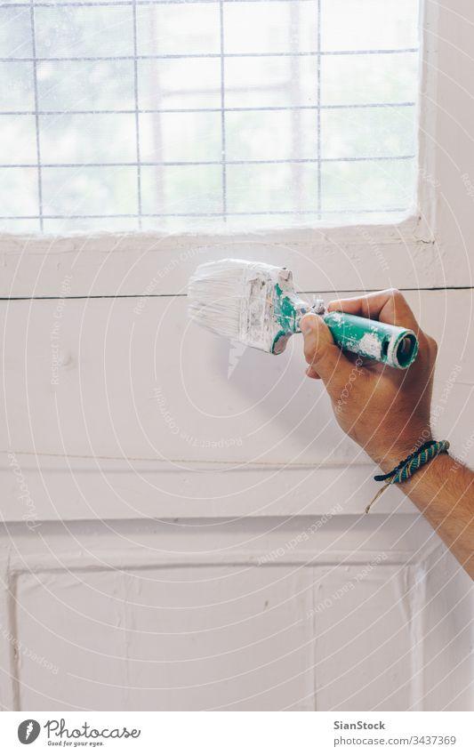 Mann malt die Wand von Hand in Weiß Malerei Farbe Haus Rolle Anstreicher weiß heimwärts Arbeit dekorierend Verbesserung Innenbereich Hintergrund Werkzeug