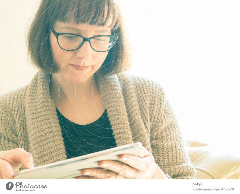 Kaukasische Frau mit Brille, die eine Tablette benutzt benutzend Arbeit von zu Hause aus Apparatur Gerät Sitzen Kaukasier Porträt konzentriert Quarantäne bob