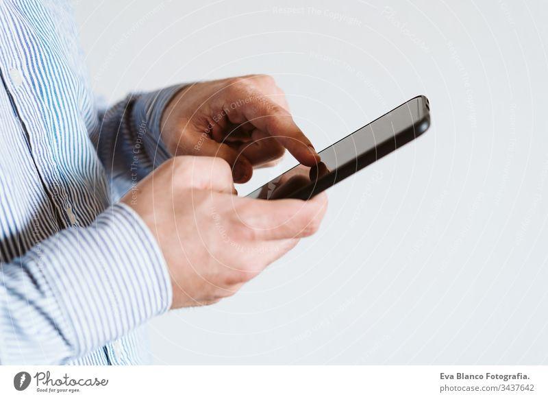 Nahaufnahme eines Mannes, der in einem Gebäude ein Mobiltelefon benutzt. Technologie-Konzept Handy unkenntlich Technik & Technologie abschließen Drahtlos Hemd