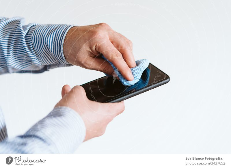 Nahaufnahme eines Mannes, der sein Mobiltelefon mit Desinfektionsmittel reinigt. Hygiene- und Coronavirus covid-19-Konzept Sauberkeit Handy Corona-Virus