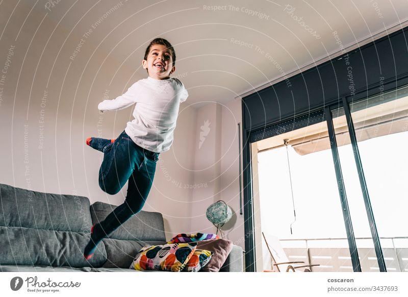 Lustiges Kind, das vom Sofa springt Aktion bezaubernd allein schön lässig Kaukasier heiter Kindheit Textfreiraum Liege niedlich häusliches Leben Energie Genuss