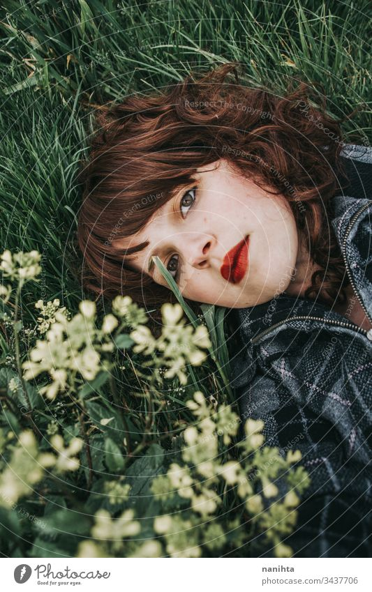 Junge schöne Frau ruht in einem Blumenfeld Porträt Stimmung Frühling dunkel romantisch Nostalgie Gefühle grün brünett hübsch Gesicht weiß Kaukasier Natur