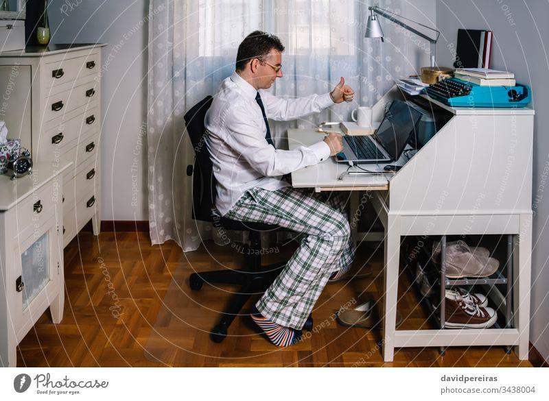 Mann bei der Telearbeit mit Hemd, Krawatte und Pyjamahose von zu Hause aus arbeiten Videoanruf Vereinbarung Coronavirus Seuche Quarantäne covid-19 Business