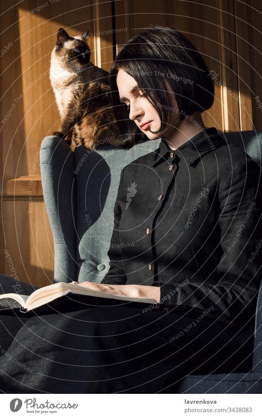 Porträt einer jungen erwachsenen Frau, die auf einem Stuhl sitzt und mit ihrer Katze hinter sich Bücher liest, langsames Leben oder Freizeitkonzept. niedlich