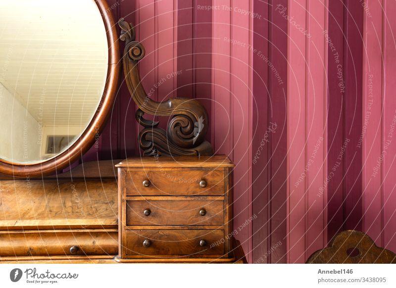 Antiker Schminktisch mit rundem Spiegel an rosa Holzwand, Retro-Design Tisch altehrwürdig Mode hölzern Schönheit Make-up Stil Schminke Hintergrund Innenbereich