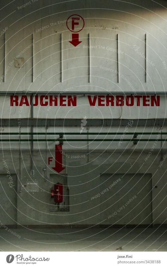 Rauchen verboten, steht in großen roten Buchstaben an der Wand der verlassenen Halle des Flugplatzes Raum alt Warnung gefährlich Feuer Feuerlöscher