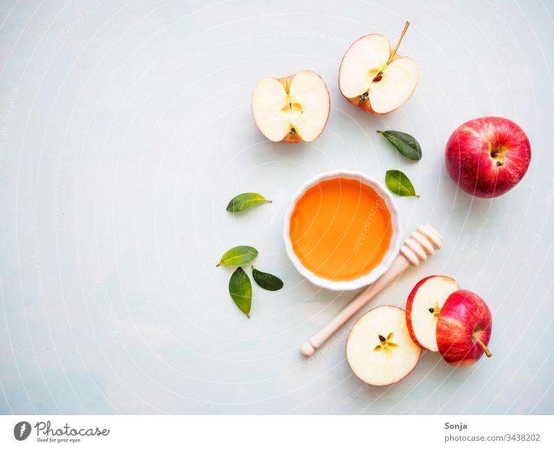 Roter halbierter Apfel und eine weiße Schüssel mit Honig auf einem hellen Hintergrund, Flachlage, gesunde Ernährung apfel verrotten honen honiglöffel draufsicht