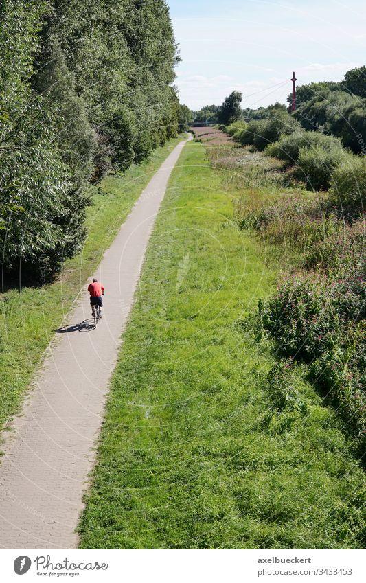 Radfahrer auf dem Radweg in der Natur Fahrradfahren Weg unkenntlich Person grün Landschaft Freizeit Erholung Sport Radfahren Aktivität im Freien Straße ländlich