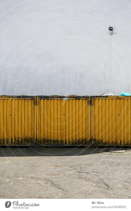Müllcontainerbox Müllbehälter gelb Container Recycling dreckig Umweltverschmutzung Wand Lampe Metall Müllabfuhr Mauer Hinterhof Schatten Hauswand