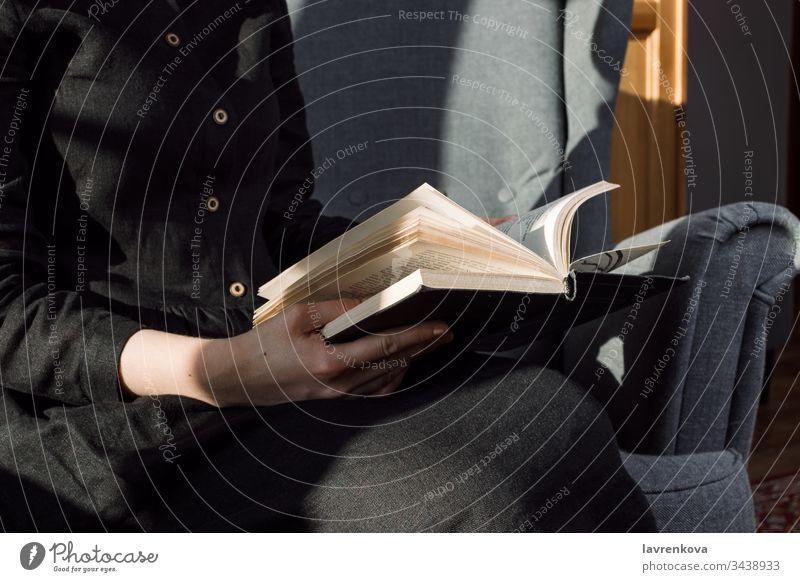 Nahaufnahme einer Frau in schwarzem Kleid, die ein Buch auf ihrem Schoss hält, selektive Fokussierung Bücher Stuhl gemütlich gesichtslos Finger Hände Hobby