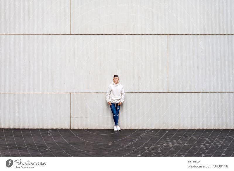Porträt eines jungen Mannes mit den Händen auf der Tasche, die außen an der Wand lehnen im Freien grau Lächeln Glück Lehnen 20s horizontal Erwachsener