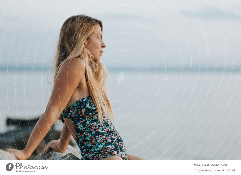 Junge Frau genießt Sonnenuntergang am Strand allein schön Windstille Küste Morgendämmerung verträumt Abenddämmerung genießen Genuss Freiheit Zukunft Mädchen