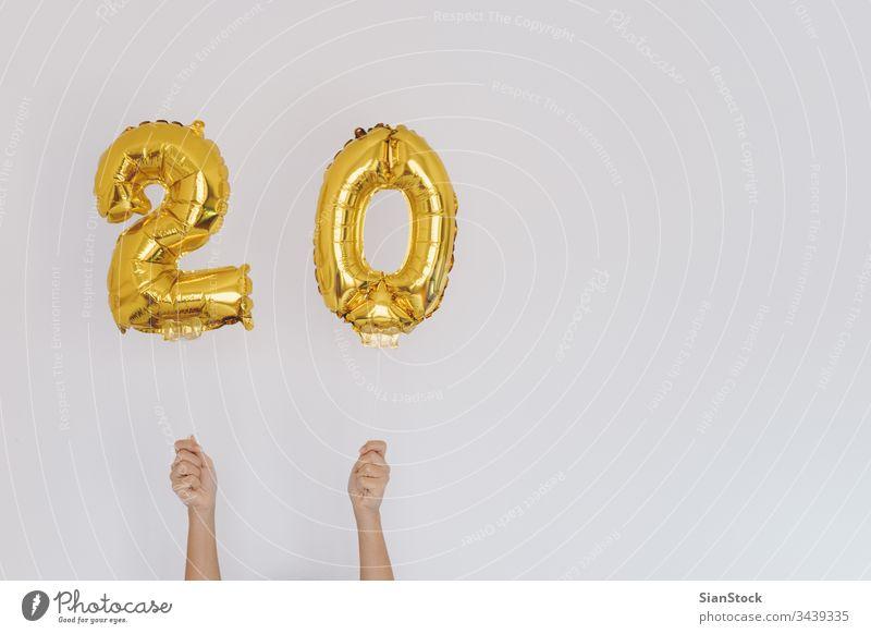Hände halten goldene 20er-Ballons, Geburtstagskonzept Jahre neu Glück Luftballon vereinzelt Halt Beteiligung Wand Gold-Zahlen-Ballons weiß fröhlich Feiertag