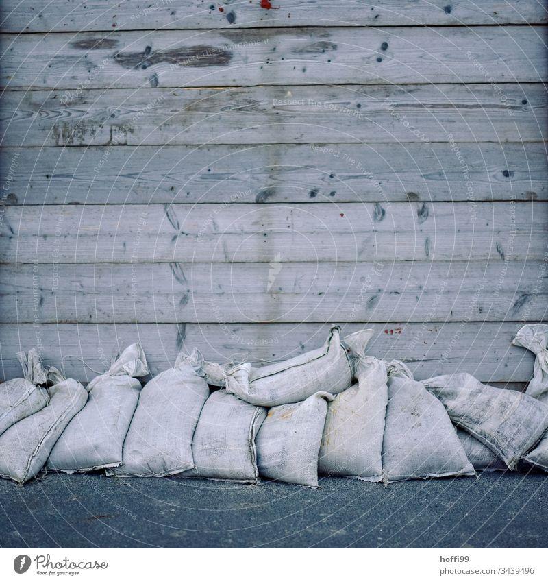 vor der Flut - Sandsäcke vor Bretterverschlag Küste fluten Minimalismus Nordsee Sandsack schützen Überflutung Hochwasser Hochwasserschutz sturmflut Klimawandel